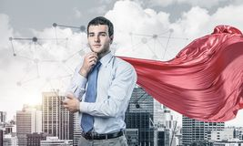 Concept of power and sucess with businessman superhero in big city. Young pensive businessman wearing red cape against modern city background royalty free stock image