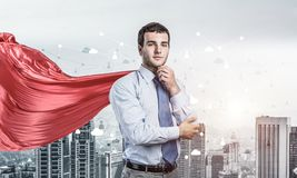 Concept of power and sucess with businessman superhero in big city. Young pensive businessman wearing red cape against modern city background stock images