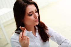 Young pensive businesswoman eating chocolate Royalty Free Stock Photography