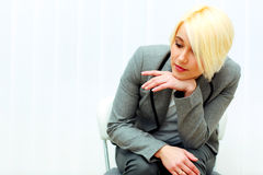 Young pensive businesswoman sitting at the chair and looking down Royalty Free Stock Images