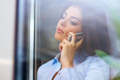 Young pensive businesswoman talking on phone Stock Photos