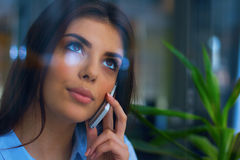 Young pensive businesswoman talking on phone Royalty Free Stock Photos