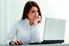 Young pensive businesswoman working on her workplace Stock Photography