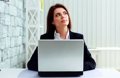 Young pensive businesswoman working on laptop Stock Photos