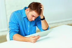 Young pensive casual businessman looking at the tablet computer Royalty Free Stock Photos