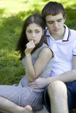 Young pensive couple sitting on grass Stock Photography