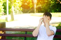 A young pensive European guy in a white T-shirt speaks on the phone and sits on a bench in the city park. covers his face with his royalty free stock image