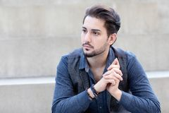 A young pensive fashionable male sitting on the concrete bleachers on the street stock photos