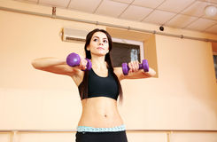 Young pensive fit woman doing exercises with dumbells Stock Photography