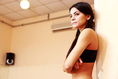 Young pensive fit woman. At gym Royalty Free Stock Image