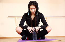 Young pensive fit woman sitting on the yoga mat Royalty Free Stock Photos
