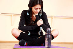 Young pensive fit woman sitting on the yoga mat Royalty Free Stock Photo