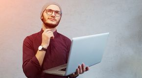 Young pensive guy holding laptop in hands over white background. Dressed in shirt and silver hat, wearing glasses. Young pensive guy holding laptop in hands royalty free stock image