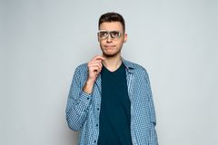 Young pensive guy posing with fake glasses royalty free stock images