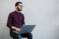Young pensive guy using laptop, wearing glasses on background of white. royalty free stock photography