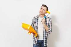 Young pensive handsome man in casual clothes holding paint tray and paint roller for wall painting isolated on white royalty free stock image