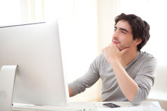 Young pensive man in front of computer. View of  a young pensive man in front of computer Stock Photos