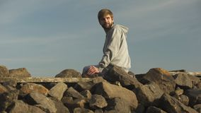 Young pensive man looking back at past, sitting on rocky hill, analyzing life. Stock footage stock video footage