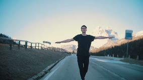 Young pensive man riding on the road and keeps balance in a small skateboard in the middle of the Alps. Mid shot stock footage