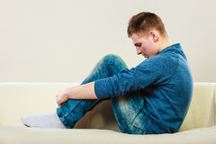 Young pensive man sitting on couch Stock Images