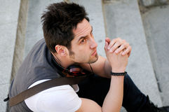 Young pensive man sitting on steps Royalty Free Stock Photography