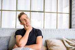 A young pensive man on the sofa in a loft style apartment Royalty Free Stock Photo