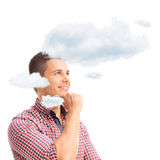 Young pensive man thinking with his head in clouds Royalty Free Stock Image