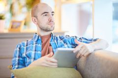Pensive man with tablet. Young pensive man with touchpad sitting in cafe and looking through window at leisure Royalty Free Stock Photos