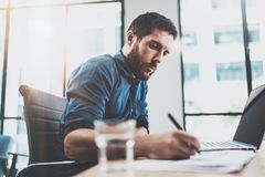 Young pensive man working at sunny loft office on laptop.Businessman making notes on paper documents reports.Blurred Stock Images