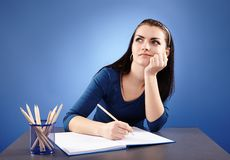 Young pensive student sitting at her desk Royalty Free Stock Image
