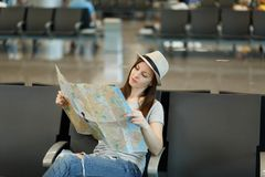 Young pensive traveler tourist woman holding paper map, search route waiting in lobby hall at international airport. Passenger traveling abroad on weekends stock photos