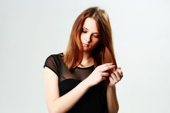 Young pensive woman caring for her hair Royalty Free Stock Photos