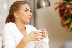 Young pensive woman drinking coffee Stock Photos