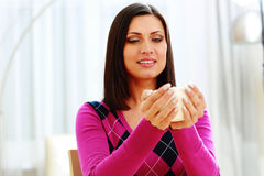 Young pensive woman holding cup of coffee Stock Images