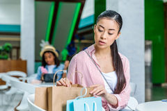 Young pensive woman looking in shopping bags, boutique shopping concept. Beautiful young pensive women looking in shopping bags, boutique shopping concept Stock Images