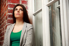 Young pensive woman looking up near brick wall Stock Photo