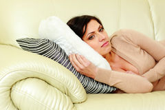 Young pensive woman lying on the sofa Royalty Free Stock Photos