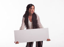 Young pensive woman showing presentation, pointing on placard Royalty Free Stock Photography