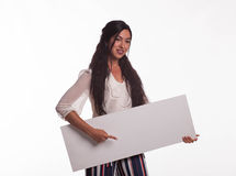 Young pensive woman showing presentation, pointing on placard Royalty Free Stock Images