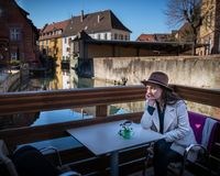 Young pensive woman sits at the table in cafe on the terrace royalty free stock images