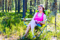 Young pensive woman sitting in a chair on the woods. Royalty Free Stock Photography