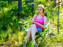 Young pensive woman sitting in a chair on the woods. Stock Image
