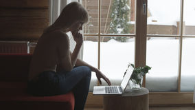 Young pensive woman sitting on the couch while typing and reading emails on the laptop with winter background on the window. Young woman with computer sitting Stock Photography