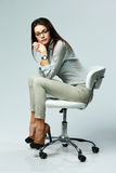 Young pensive woman sitting on the office chair Royalty Free Stock Images