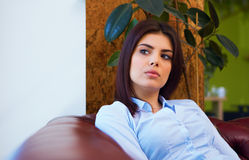 Young pensive woman sitting on the sofa Royalty Free Stock Images