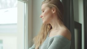 Young pensive woman standing by a window. stock footage