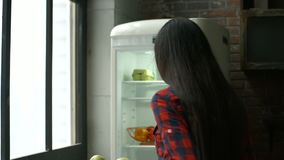 Young pensive woman taking food out of fridge stock video
