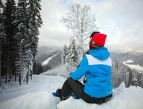 Young pensive woman in winter in snowy forest on top of mountain Stock Photos