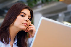Young pensive woman working with laptop Stock Photo