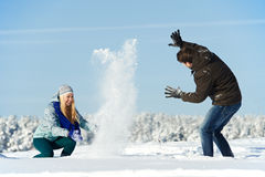 Young peolple playing with snow in winter. Happy young people playing with snow splashes in sunny winter outdoors Royalty Free Stock Photos